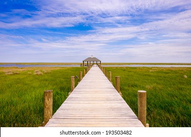 Long boathouse pier over marshland in rural Louisiana.