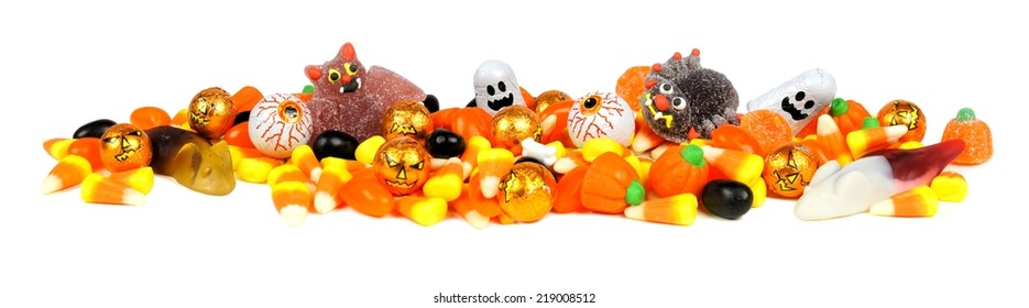 Long border of assorted Halloween candy over white