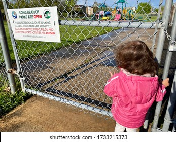 LONG BRANCH, NEW JERSEY - MAY 10, 2020 - Little girl cannot play on playground as closed due to Covid-19 Coronavirus prevents children from spreading germs to slow the spread of the coronavirus