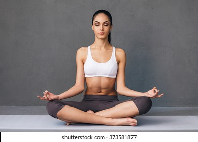 Long breath in. Beautiful young African woman in sportswear practicing yoga while sitting in lotus position against grey background