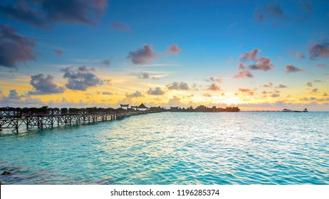 Long bridge heading to beautiful resort at Mabul Island during sunset