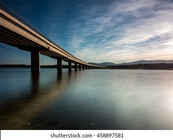 Long bridge over a lake with still water at evening, blue hour (calm scene, serenity concept)
