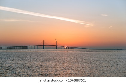 Long bridge with sunset or sunrise behind - orange,red, blue and yellow skies