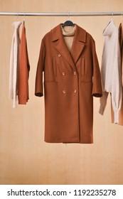 long brown coat ,sweater on hanger –wooden background.