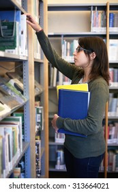 long brown hair girl with black glasses holding books with bookshelf on background. portrait of female student in a library taking a bast from shelves