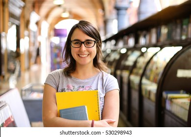 long brown hair girl with black glasses holding book and smiling. portrait of female student in hold town