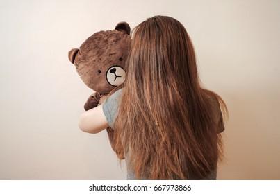 Long  brown hair girl hugging the brown teddy bear with sad feeling.