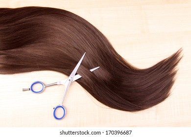 Long brown hair and scissors on wooden background