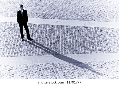 Long businessman shadow in urban background.