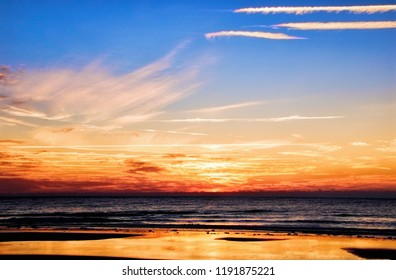 Long camera exposure captures the morning beauty of a sunrise over the horizon of the Atlantic Ocean on the east coast of America in Myrtle Beach South Carolina.