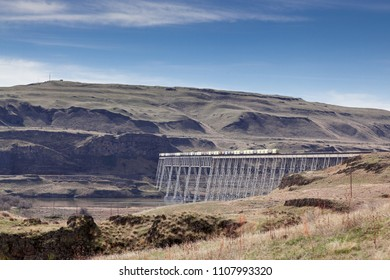 A long cargo train crossing a railway bridge that crosses the Snake River in the rocky and dry barren landscape of Eastern Washington.