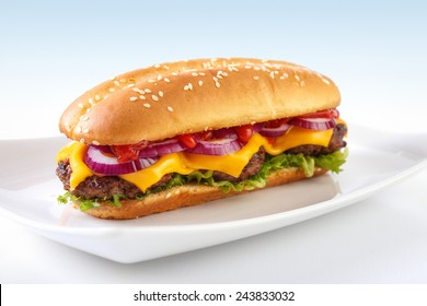 Long cheeseburger on plate , with three grilled patties , lettuce ,  red onion , cheddar cheese and ketchup