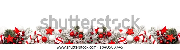 Long Christmas border of red and white ornaments and frosty branches isolated on a white background