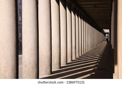 Long colonnade in baroque style in afternoon sun with long shadows.