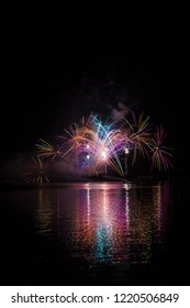 Long colorful tails of fireworks over surface Brno's Dam with lake reflection