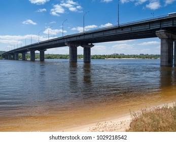 Long concrete bridge across the wide river with sandy shore. Bottom view