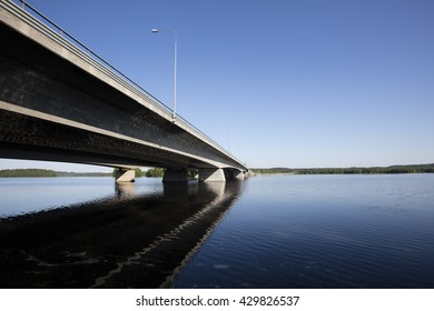 A long concrete bridge, which extends to the horizon in Finland. The bridge crosses the lake. It is noon and the weather is clear and sky is blue. Focal point is the bridge.