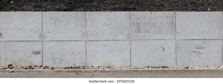 A long concrete wall supports the  slope and protects the earth from shedding.  Panoramic collage from several outdoor photos