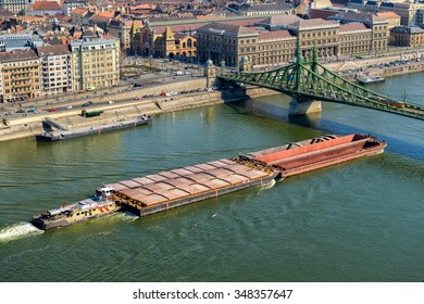 Long container ship sailing under the the bridge