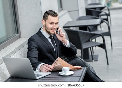Long conversation. Telephone conversation of a young man with a beard and in a business suit with a cup of coffee.