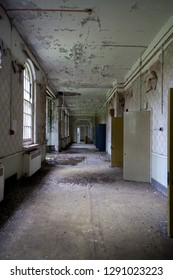 Long coridor and open cell doors at an abandoned and derelict lunatic asylum/hospital (now demolished), Cane Hill, Coulsdon, Surrey, England, UK