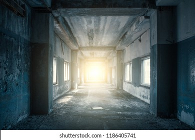 Long corridor or tunnel in haunted and ruined abandoned industrial building. Light in the end of tunnel. Way to freedom concept