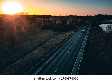 Long country road with white lines down the centre stretching off past a lone tree to the distant horizon - Shutterstock ID 1960976026