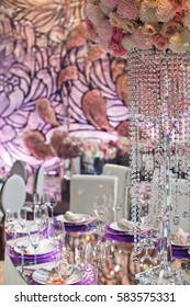Long crystal chains hang from colorful bouquet over dinner table