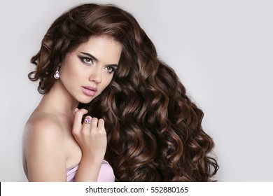 Long curly hair. Beautiful Brunette girl portrait with long shiny wavy hairstyle. Fashion elegant model woman with diamond jewelry set. Curling Iron Hair Curler Styling.