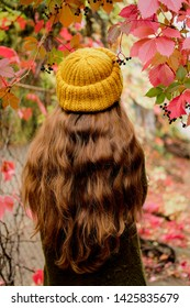 Long curly hair in mustard yellow knit hat. Casual style for autumn season