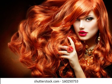 Long Curly Red Hair. Fashion Woman Portrait. Beauty Model Girl with Luxurious Hair, Make up and Accessories. Hairstyle. Wavy Hair Extensions Concept. Holiday Makeup. Smoky eyes and Red lipstick