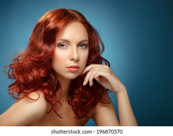 Long Curly Red Hair. Fashion Woman Portrait. Beauty Model Girl with Luxurious Hair and Make up. Hairstyle. Wavy Hair Extensions Concept. Classic Makeup.