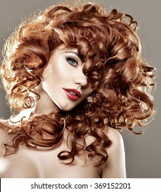 Long Curly Red Hair. Fashion Woman Portrait. Beauty Model Girl with Luxurious Hair. Hairstyle. Red lipstick