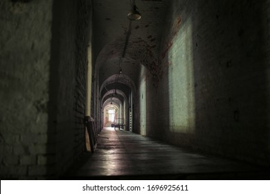 A long, dark corridor in an old abandoned fort. Stone walls. Shadow and light from small windows.  There is an old, iron gurney against the wall