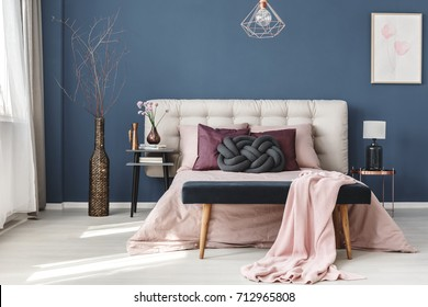 Long decorative dark vase with branches next to bedside cabinet in pastel bedroom with blue wall
