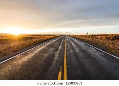 Long desert highway at the sunset