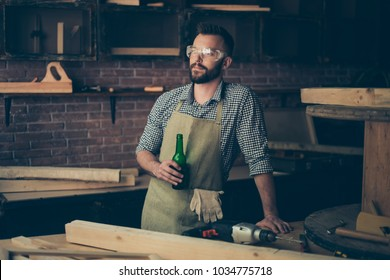 So long desired break after working day! Happy satisfied successful peaceful calm cabinet maker is drinking beer from bottle in his hand, he is enjoying his relaxation