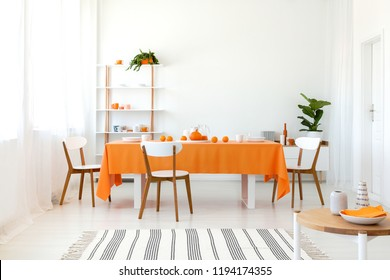 Long dining room table covered with orange tablecloth and comfortable white chairs around it.
