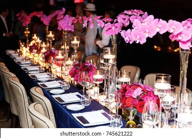 Long dinner table decorated with gold, shiny candles and red flo