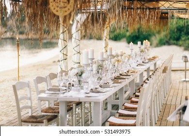 Long dinner table prepared for wedding party stands under beach umbrellas