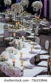 Long dinner table with white flower garlands, shiny candles on silver candleholders, golden glasses and violet cloth