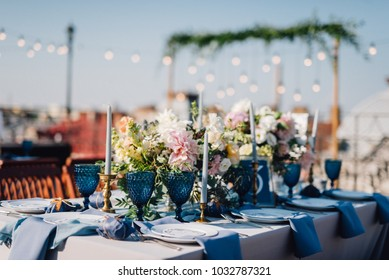 Long dinner tables covered with grey and blue cloth, served with porcelain and blue glasses and rich decorated with flowers stand on the roof of a house. Bokeh lights on baclground