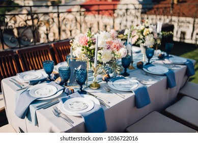 Long dinner tables covered with grey cloth, served with porcelain and blue glasses and rich decorated with flowers stand on the roof of a house. Rustic decor. Wedding