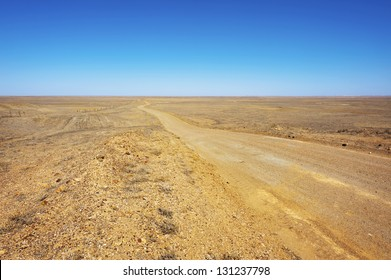 A long dirt road leads further into the arid desert.