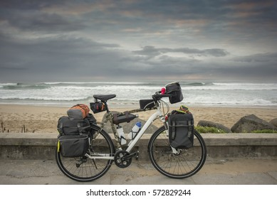 A long distance bicycle stand parked against a low wall next to the road with the ocean in the background