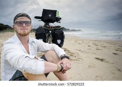 A long distance cyclist sits on the beach with his arms on his legs, looking out in to the distance while his bicycle with panniers stand behind him.