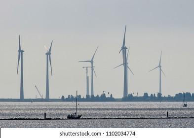 Long distance view of large wind turbines, one under construction, with a small yacht in the foreground, at Lake Grevelingen in The Netherlands