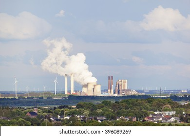 Long distance view over rural landscape to a steaming coal-fired power station.