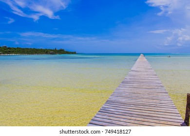 The Long Dock in Cherokee Sound, Marsh Harbour, Abaco, The Bahamas. Old wooden dock stretches out over sea with beautiful blue sky in the background.