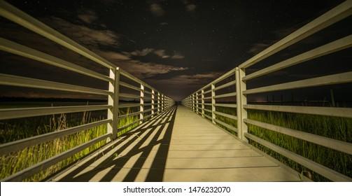Long dock with the dark night sky